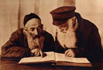 Two venerable Jews poring over a Hebrew religious work in Pinsk, Poland.